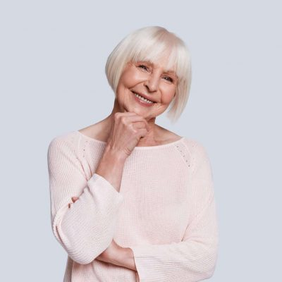 True feminine beauty. Beautiful senior woman keeping hand on chin and smiling while standing against grey background
